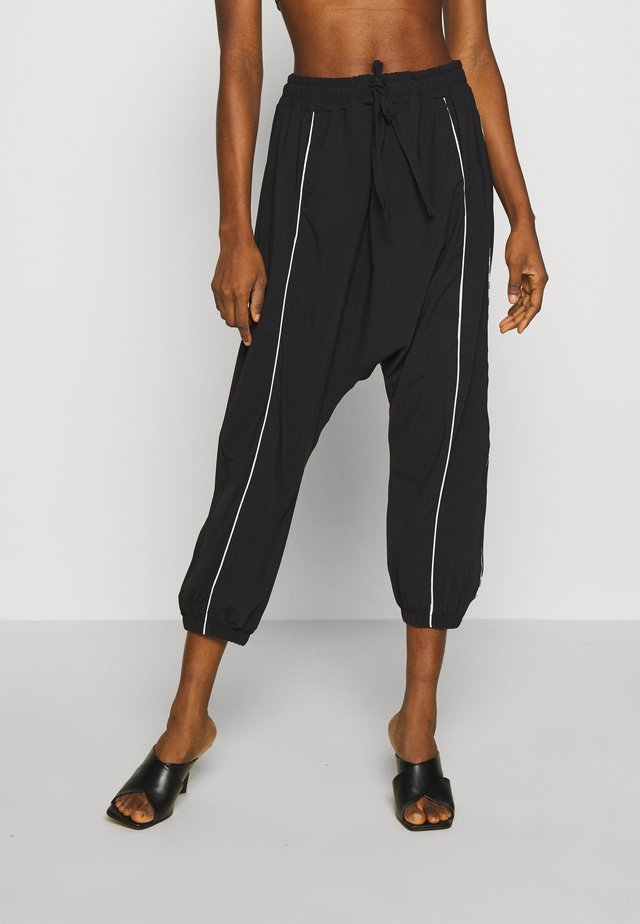 DROPPED PANTS - Tracksuit bottoms - black