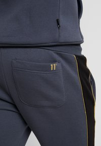 11 DEGREES - SKINNY  - Tracksuit bottoms - black/anthracite/goldpiping - 6