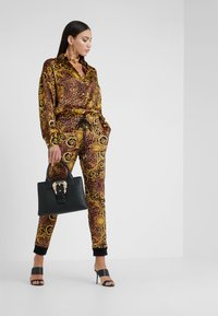 Versace Jeans Couture - Tracksuit bottoms - gold - 1