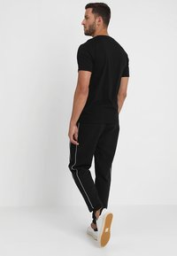 Calvin Klein - EMBROIDERY PANT - Tracksuit bottoms - black - 2