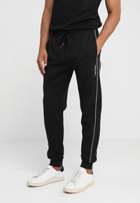 Calvin Klein - EMBROIDERY PANT - Tracksuit bottoms - black - 0