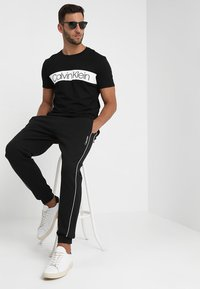 Calvin Klein - EMBROIDERY PANT - Tracksuit bottoms - black - 1