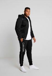 Calvin Klein - LOGO PRINT PANT - Teplákové kalhoty - black - 1
