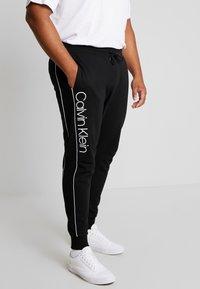 Calvin Klein - LOGO PRINT PANT - Tracksuit bottoms - black - 0
