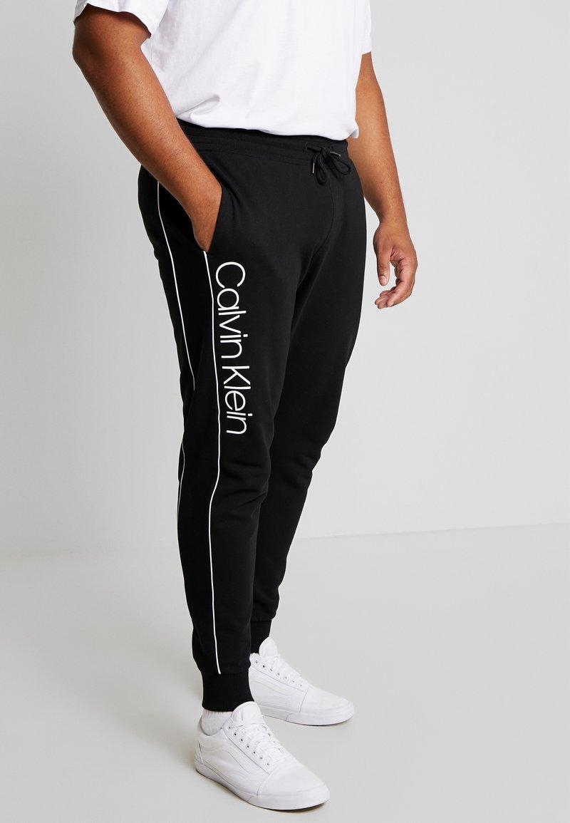 Calvin Klein - LOGO PRINT PANT - Tracksuit bottoms - black