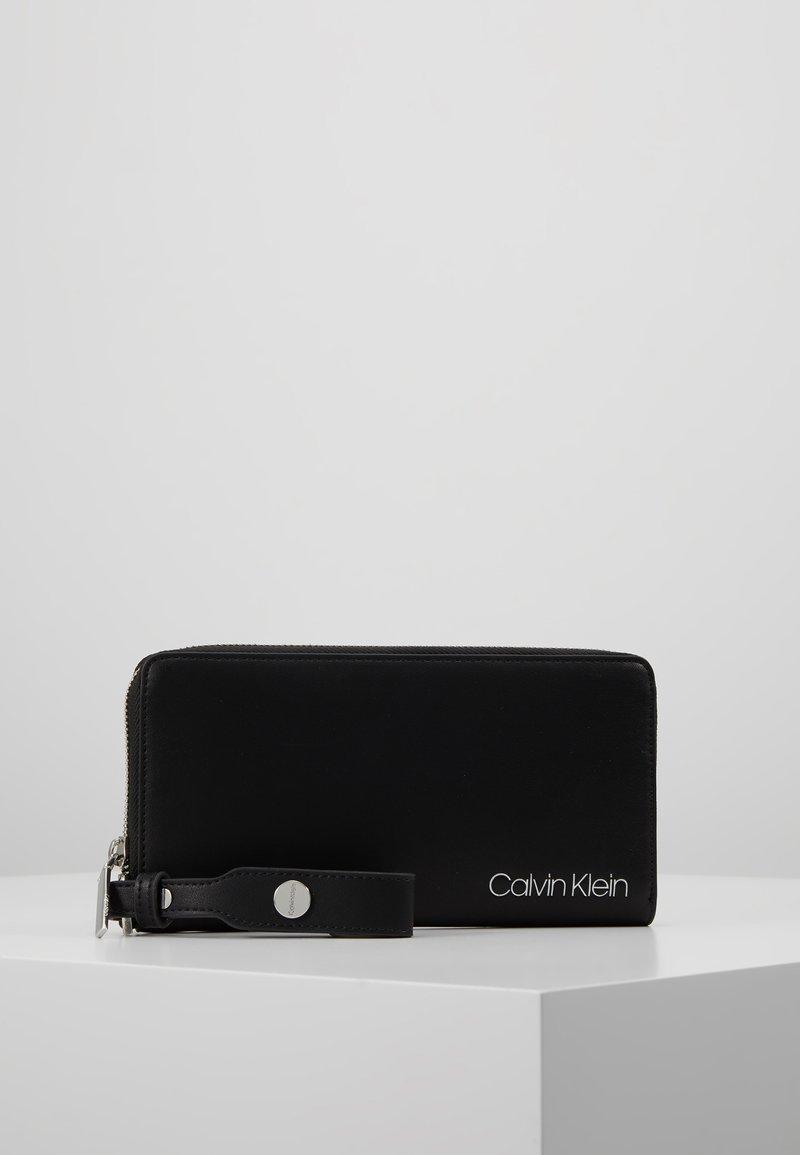 Calvin Klein - STRIDE ZIPAROUND - Geldbörse - black