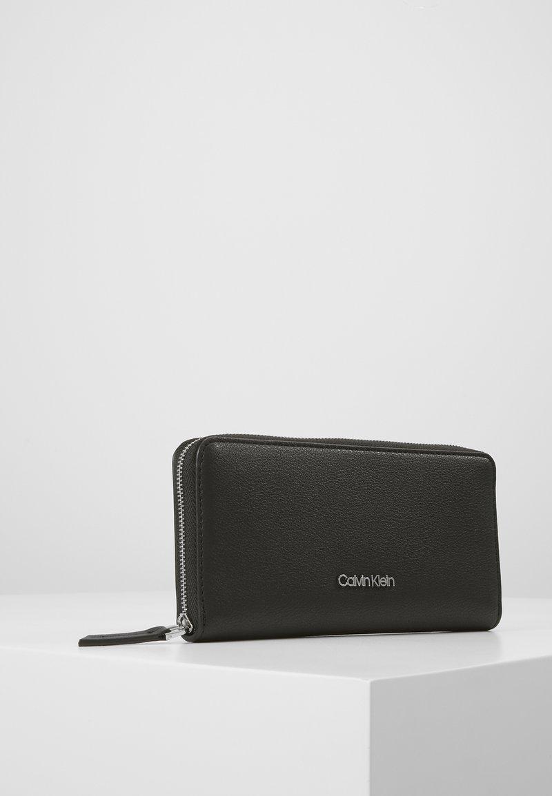 Calvin Klein - CK MUST ZIPAROUND WALLET LG - Wallet - black
