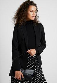 Calvin Klein - WINGED SHOULDER BAG - Handbag - black - 1