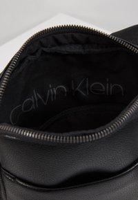 Calvin Klein - CK BOMBE' FLAT CROSSOVER - Taška spříčným popruhem - black - 4