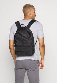 Calvin Klein - STRIPED LOGO ROUND BACKPACK - Rugzak - black - 1