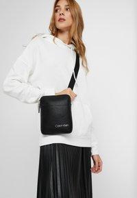 Calvin Klein - DIRECT MINI FLAT CROSSOVER - Across body bag - black - 5