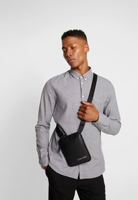 Calvin Klein - DIRECT MINI FLAT CROSSOVER - Across body bag - black - 1