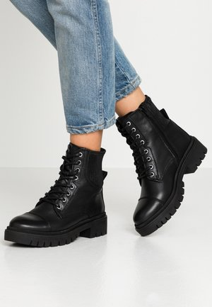 ADRIAMA - Lace-up ankle boots - black