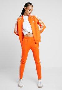 adidas Originals - Tracksuit bottoms - orange - 1