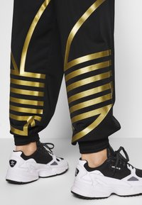 adidas Originals - LARGE LOGO ADICOLOR TRACK PANTS - Tracksuit bottoms - black/gold - 3