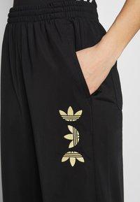 adidas Originals - LARGE LOGO ADICOLOR TRACK PANTS - Tracksuit bottoms - black/gold - 5
