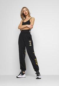 adidas Originals - LARGE LOGO ADICOLOR TRACK PANTS - Tracksuit bottoms - black/gold - 1