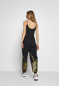 adidas Originals - LARGE LOGO ADICOLOR TRACK PANTS - Tracksuit bottoms - black/gold - 2