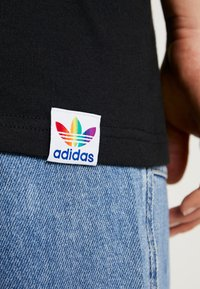 adidas Originals - PRIDE TEE - T-shirts med print - black/white