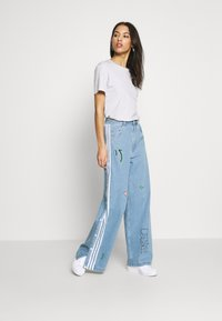 adidas Originals - TRACKPANT - Flared Jeans - clear sky - 1