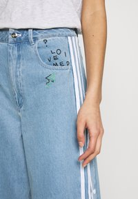 adidas Originals - TRACKPANT - Flared Jeans - clear sky - 3