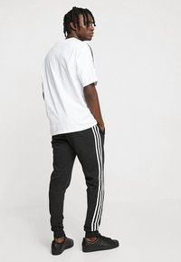 adidas Originals - STRIPES PANT - Tracksuit bottoms - black - 2