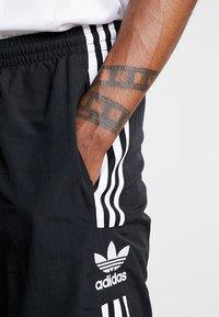 adidas Originals - LOCK UP - Tracksuit bottoms - black - 3
