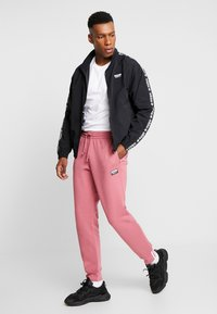 adidas Originals - REVEAL YOUR VOICE - Tracksuit bottoms - trace maroon - 1