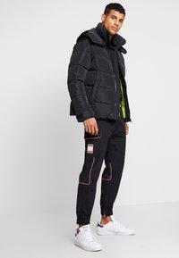 adidas Originals - REGULAR TRACK PANTS - Pantalon cargo - black - 1