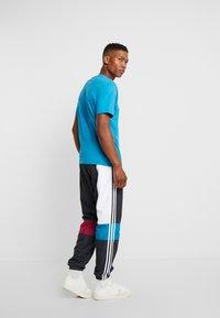 adidas Originals - TRACK PANT - Tracksuit bottoms - carbon/active teal/berry - 2