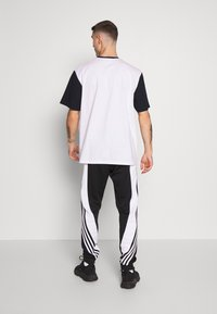 adidas Originals - 3STRIPES WRAP TRACK PANTS - Tracksuit bottoms - black/white