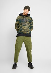 adidas Originals - CAMO TREFOIL GRAPHIC HODDIE SWEAT - Mikina s kapucí - black/multicolor - 1
