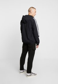 adidas Originals - OUTLINE WINDBREAKER JACKET - Kevyt takki - black - 2