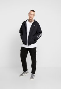 adidas Originals - OUTLINE WINDBREAKER JACKET - Kevyt takki - black - 1