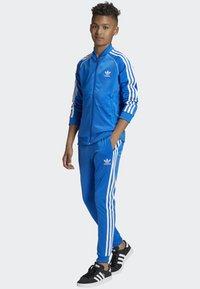 adidas Originals - SST TRACKSUIT BOTTOMS - Verryttelyhousut - blue/white - 1