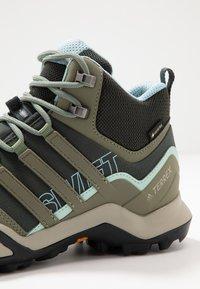 adidas Performance - TERREX SWIFT R2 MID GORE-TEX - Hiking shoes - legend erath/legend green/ash grey - 5