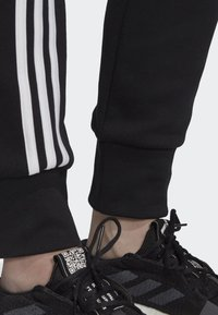 adidas Performance - MUST HAVES 3-STRIPES JOGGERS - Tracksuit bottoms - black - 3