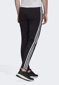 adidas Performance - Tracksuit bottoms - black - 1
