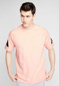 adidas Performance - HEAVY TEE - Camiseta estampada - glow pink - 0