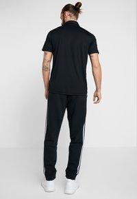 adidas Performance - Tracksuit bottoms - black/white - 2