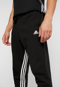 adidas Performance - Tracksuit bottoms - black/white - 4