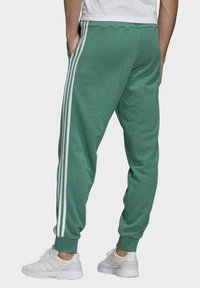 adidas Performance - ESSENTIALS 3-STRIPES TAPERED CUFFED JOGGERS - Tracksuit bottoms - green - 1
