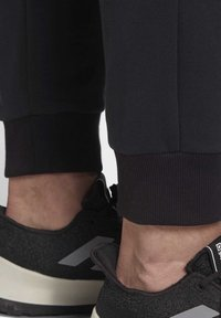 adidas Performance - MUST HAVES GRAPHIC JOGGERS - Tracksuit bottoms - black - 6