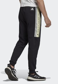 adidas Performance - MUST HAVES GRAPHIC JOGGERS - Tracksuit bottoms - black - 1