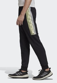 adidas Performance - MUST HAVES GRAPHIC JOGGERS - Tracksuit bottoms - black - 3