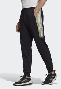 adidas Performance - MUST HAVES GRAPHIC JOGGERS - Tracksuit bottoms - black - 0