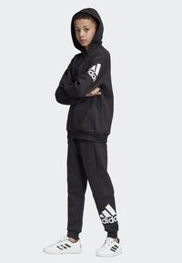 adidas Performance - MUST HAVES BADGE OF SPORT FLEECE JOGGERS - Tracksuit bottoms - black - 1