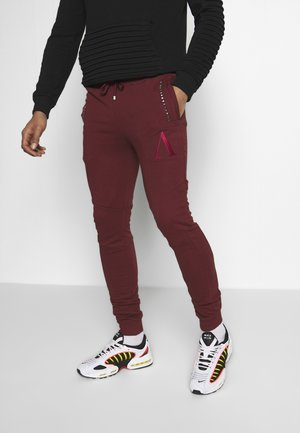 CARNAGE - Tracksuit bottoms - red