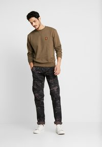 Alpha Industries - Pantalones cargo - black camo - 1