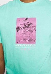 American Eagle - UNISEX SET IN TEE CORE BRAND - T-shirt z nadrukiem - cream mint - 5